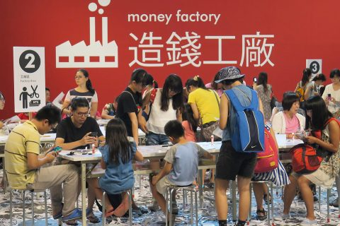 "Large group of people sitting at tables with scraps of paper littering the floor and the words ""money factory"" on the wall behind them"