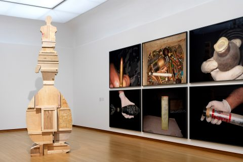 Installation view of an exhibition showing an abstract wood sculpture and photographs of instruments of war (bullets, bombs, etc.)