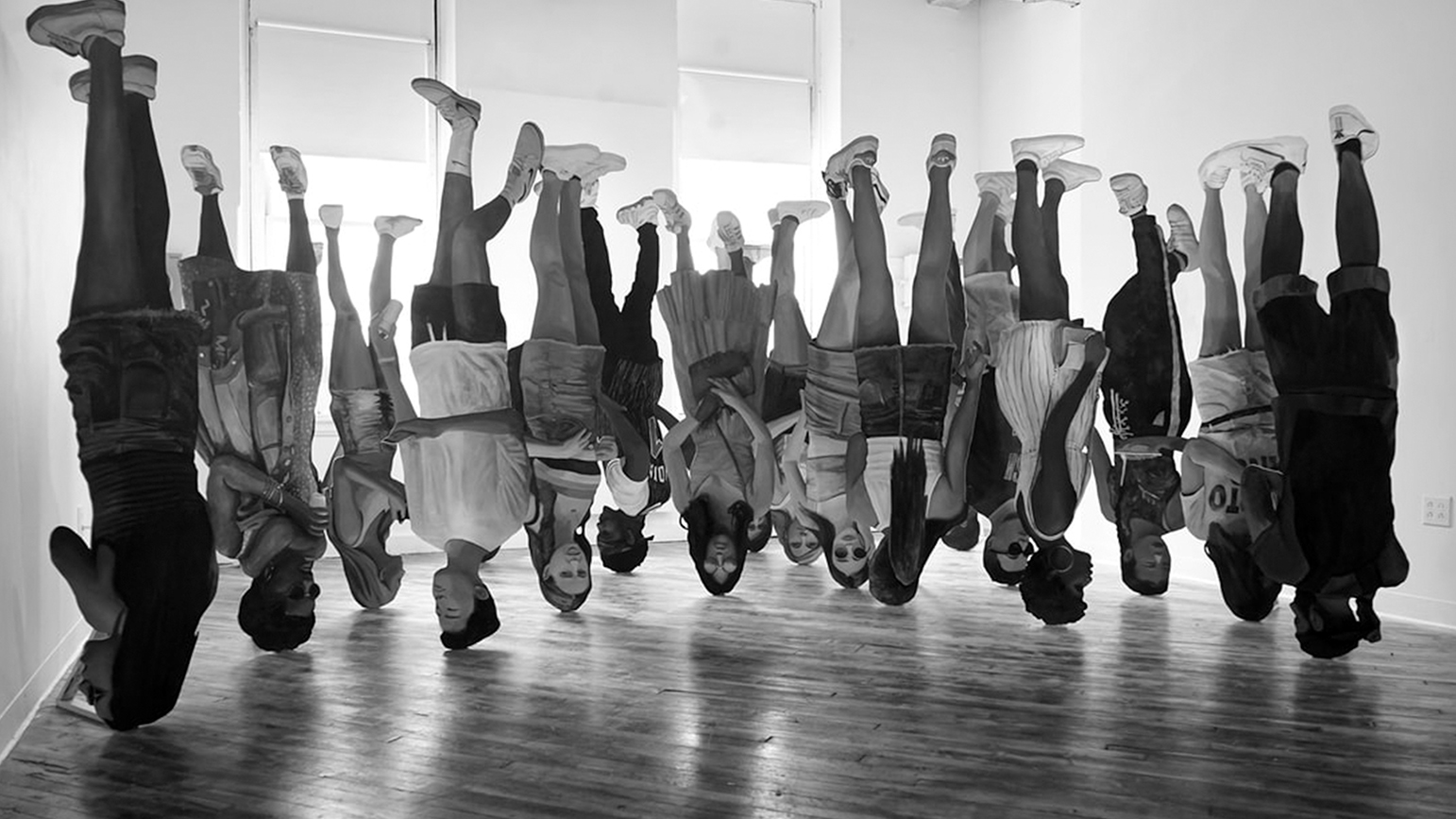 Black and white digitally-created image of a group of people upside down in an empty room