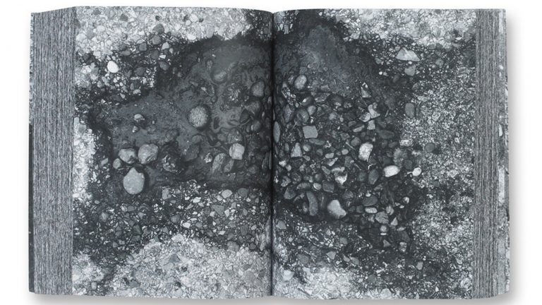 Two-page spread showing a black-and-white close-up photograph of a pothole from Kim Beck's book Pavements, Potholes & Repairs