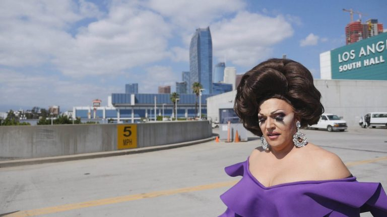 "Still from the documentary ""Workhorse Queen"" showing a drag queen with a city skyline in the background"
