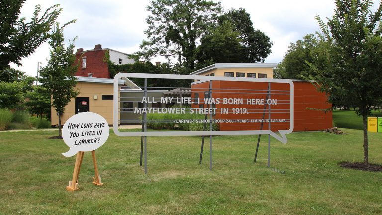 "Two large speech bubbles installed outside, one reading ""How long have you lived in Larimer"" and the other reading ""All my life. I was born here on Mayflower Street in 1919."""