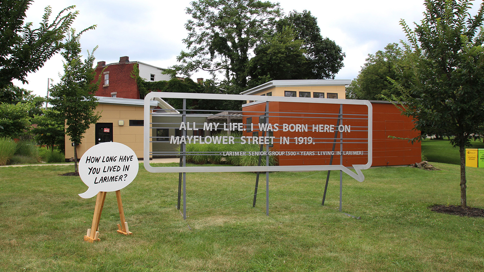 """Two large speech bubbles installed outside, one reading """"How long have you lived in Larimer"""" and the other reading """"All my life. I was born here on Mayflower Street in 1919."""""""