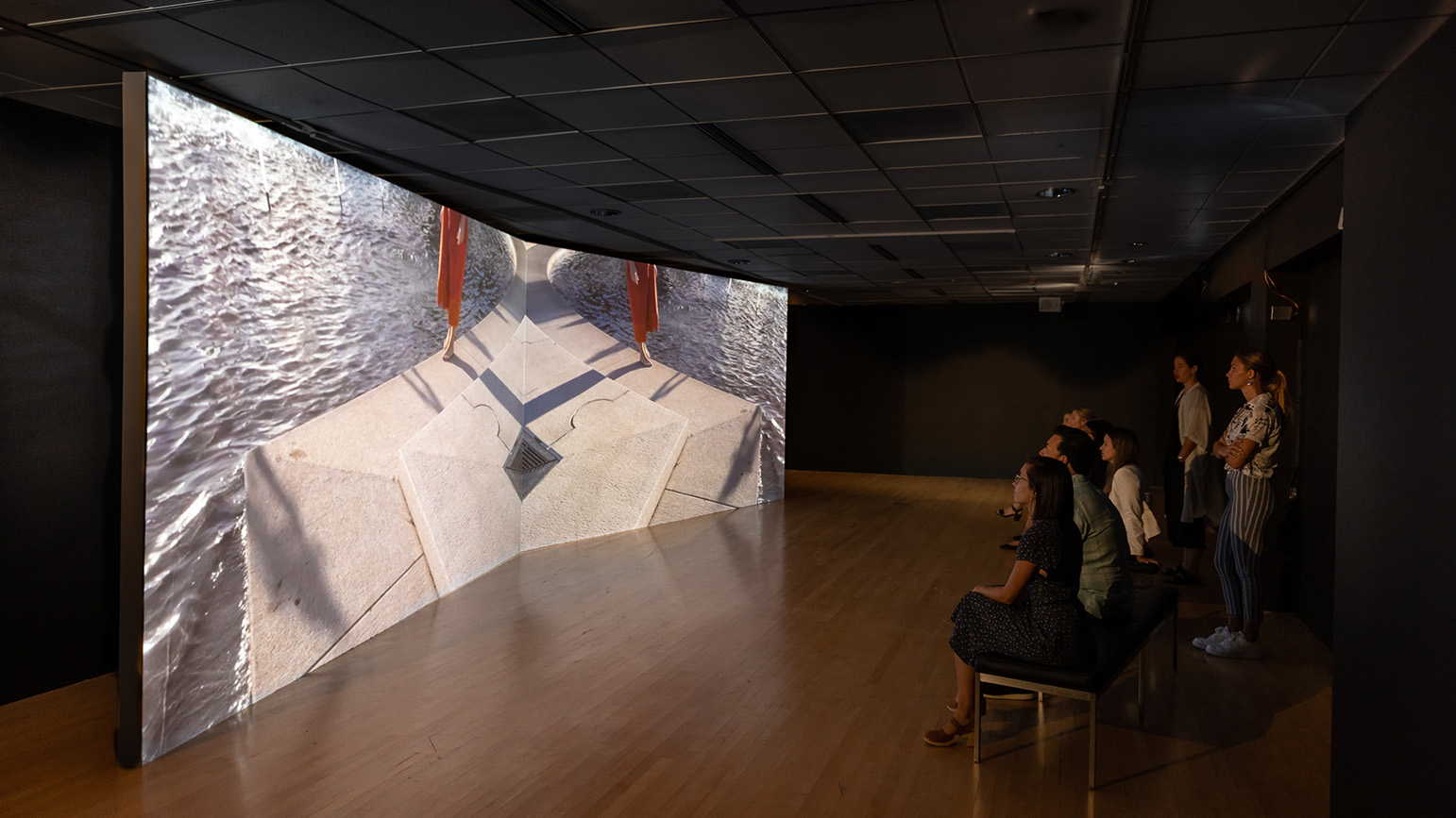 People in a gallery watching a projection on a massive screen