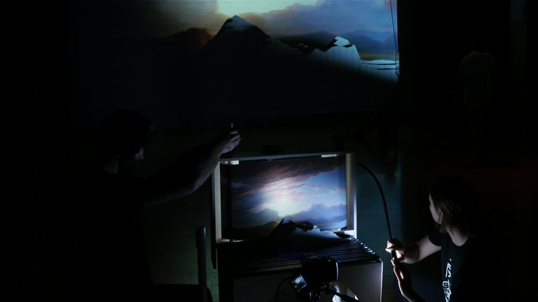 Two people running a projection with a mountain scene