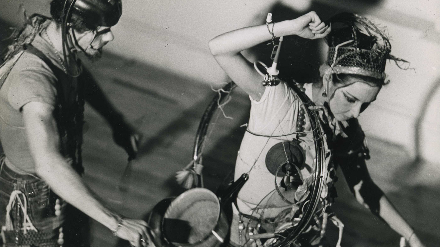 Black-and-white image of two performers with sound making devices attached to themselves
