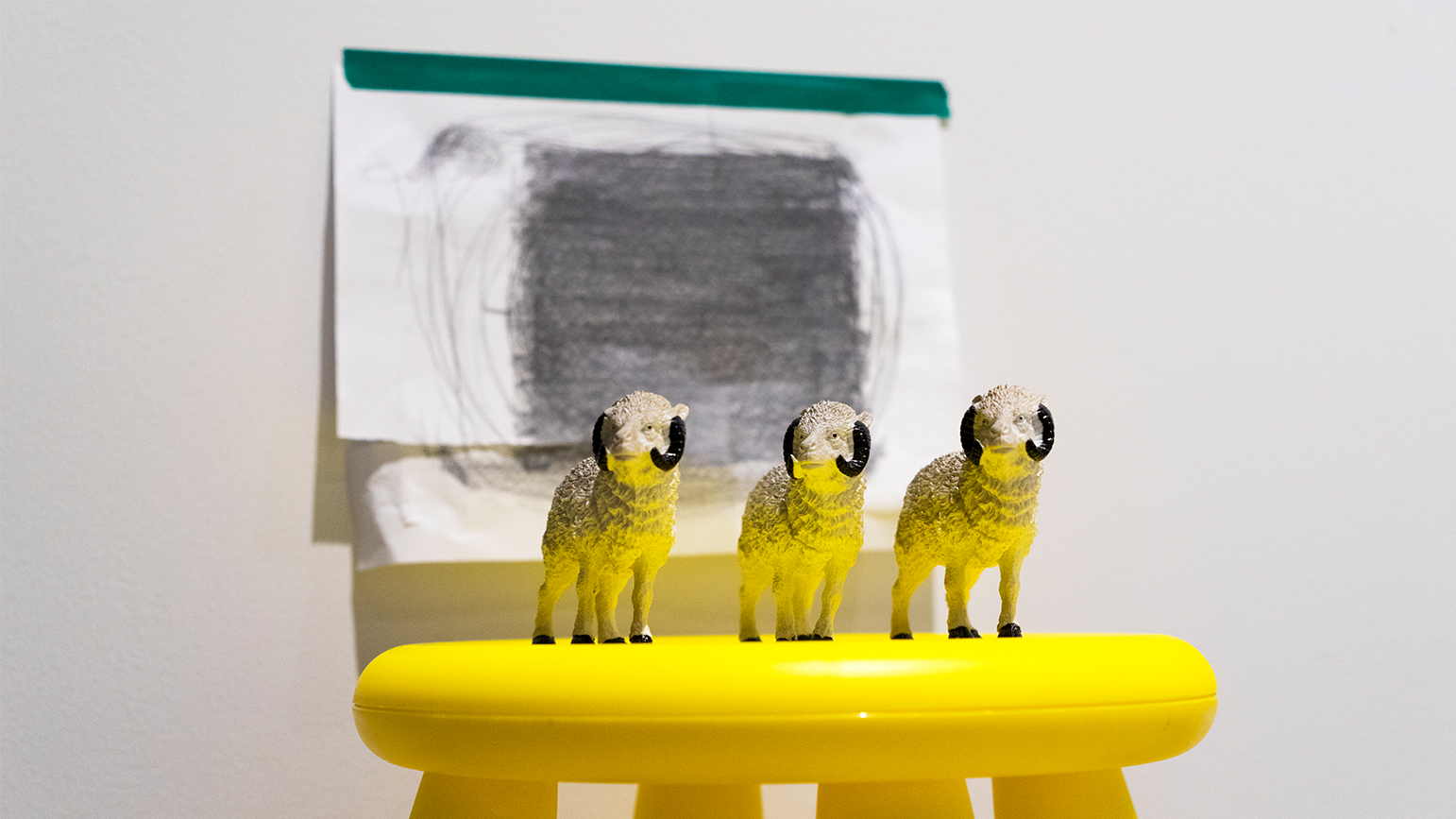 Three ram figurines on a stool with a drawing of a square taped on the wall behind