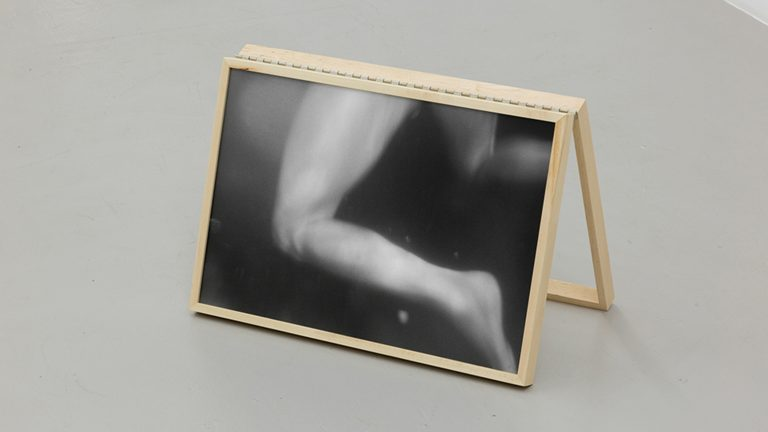 Black and white photograph of legs swimming, installed on a simple wooden easel on a gallery floor