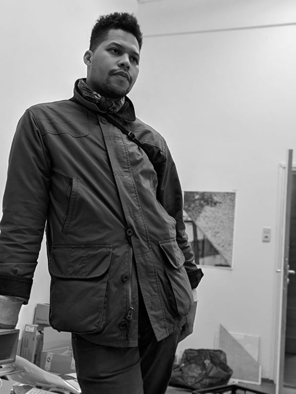 Black and white photograph of Lyndon Barrois Jr. standing in his studio