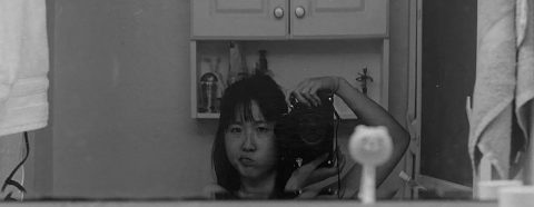 Black and white photograph of Diane Lee taken in a bathroom mirror
