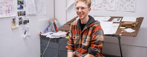 Photograph of Josh Kery sitting in his studio