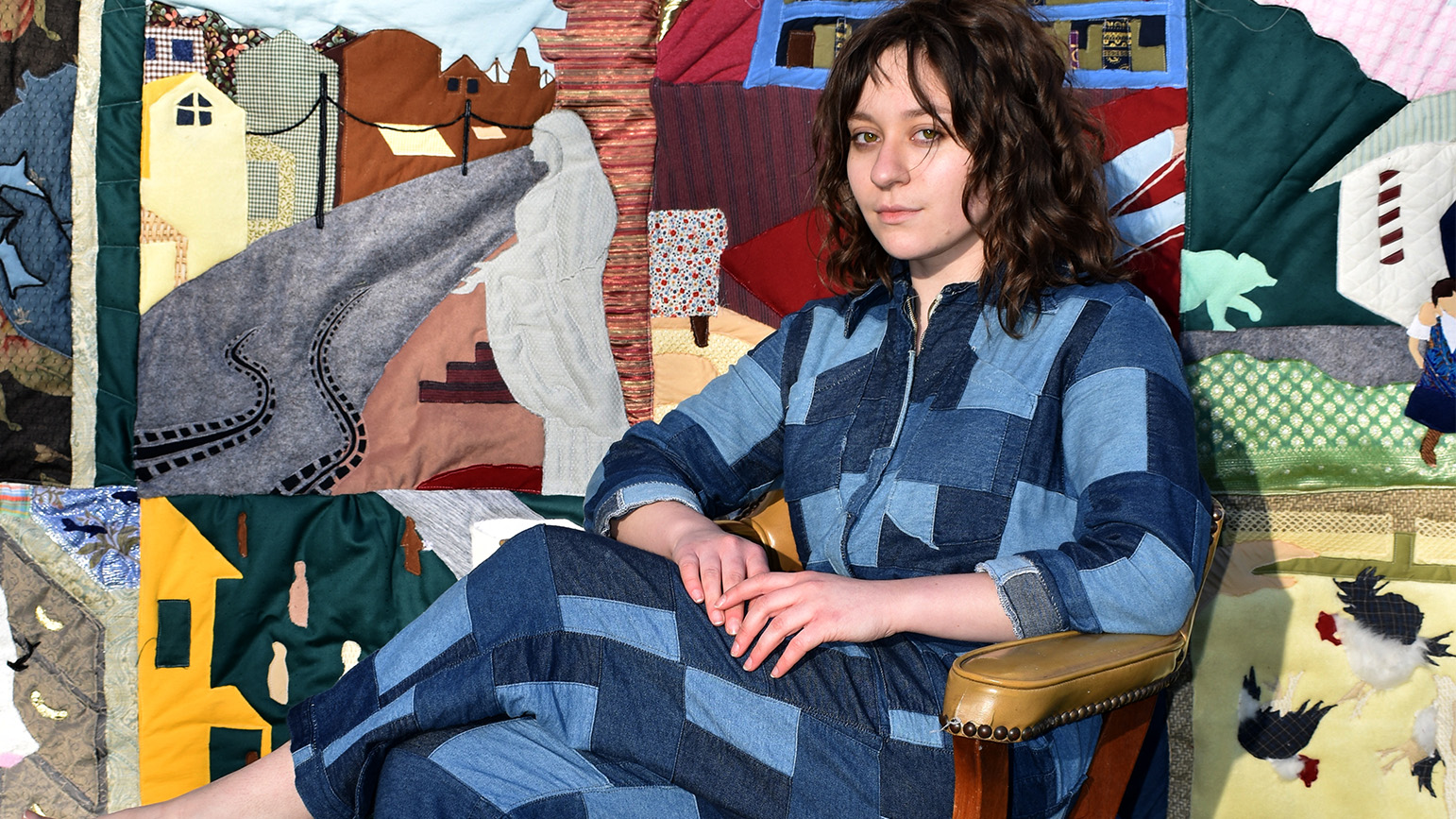Photograph of Miranda Miller in a denim patchwork jumper in front of her family stories quilt