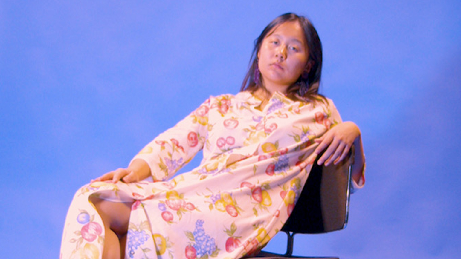 Image of Nana Cheon leaning back in a chair against a blue background