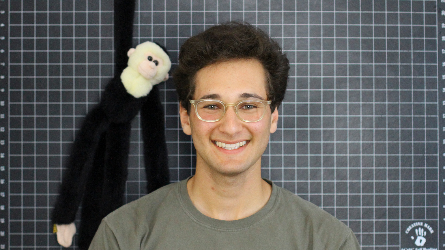 Headshot of Zachary Rapaport in front of a grid mat and with a stuffed monkey