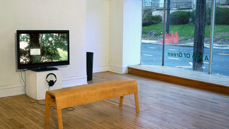 Installation image of The Frame showing a video with bench in front