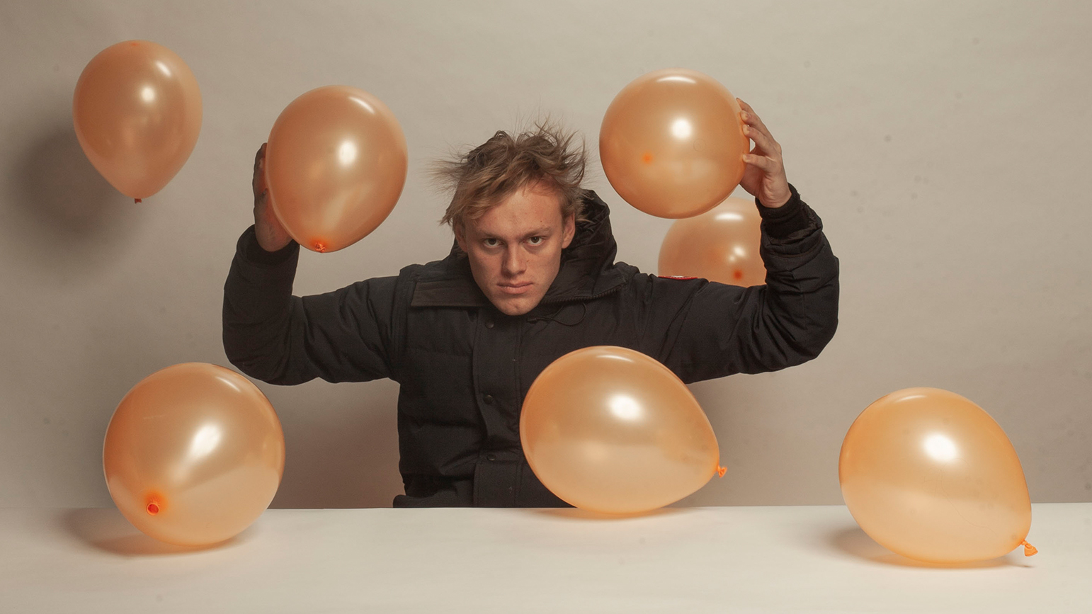 Photograph of Jackson Bridgers surrounded by balloons
