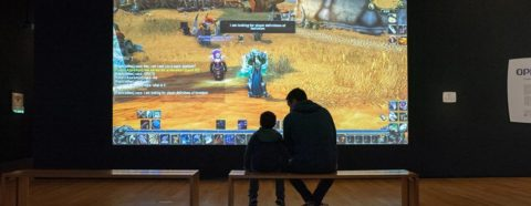 "A child and adult sitting on a bench looking at a projection of the video game ""World of Warcraft"""