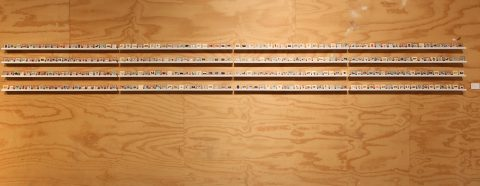 "Installation view of ""300 non-instagrams"" showing four long shelves with 300 collages the size of film slides"