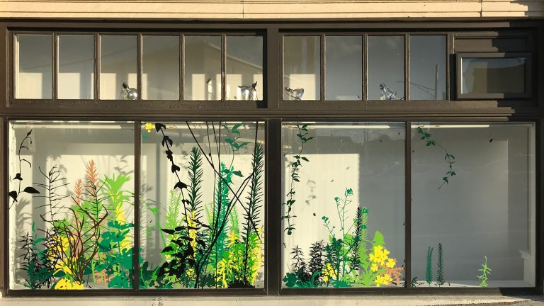 Storefront windows with vinyl cutouts of various plants