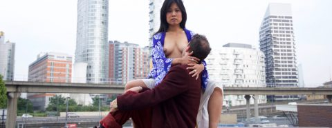 "Image from Lena Chen's ""Nurture"" showing a person at the exposed breast of the artist"