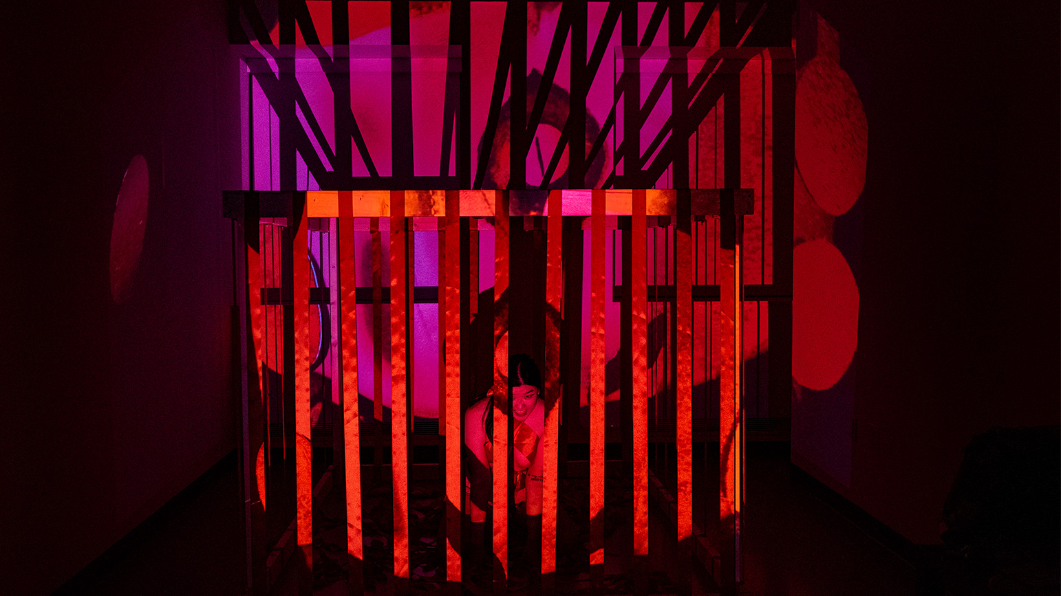 In a dark space with bright red and link light, a person is behind bars
