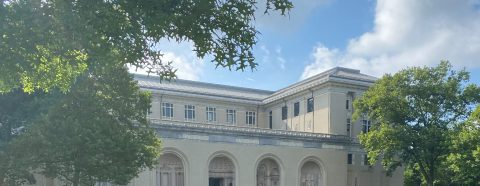 Photograph of the exterior of CMU's College of Fine Arts, a beaux-arts building with large trees in front