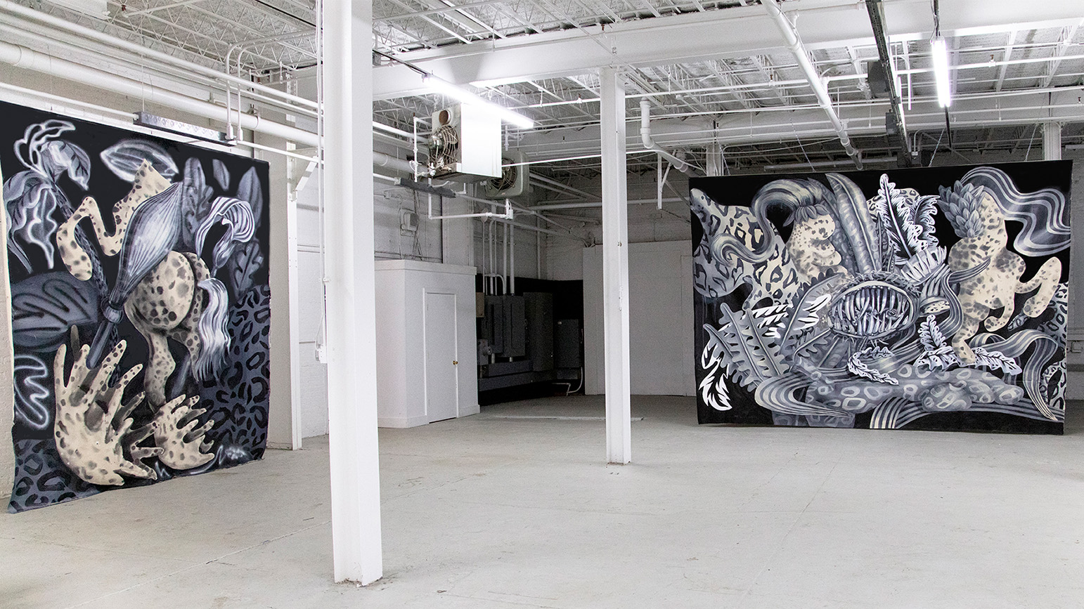 Two large abstract paintings in grisaille installed in a warehouse
